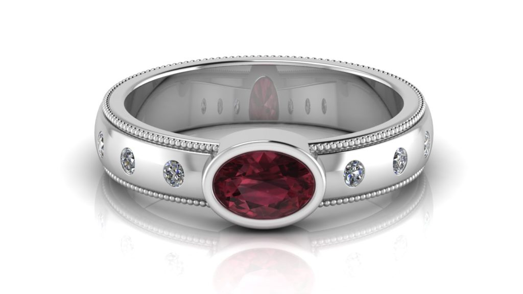 White gold ring featuring a bezel set garnet, flush set diamonds and milgrain accents