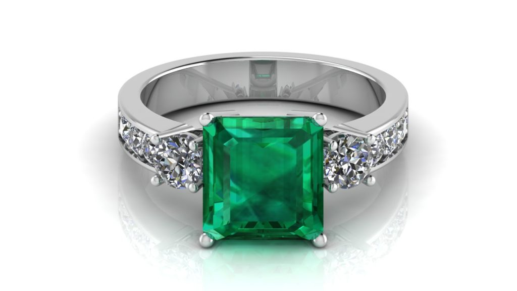 White gold three stone ring featuring an emerald with two round side diamonds and pave set diamond accents