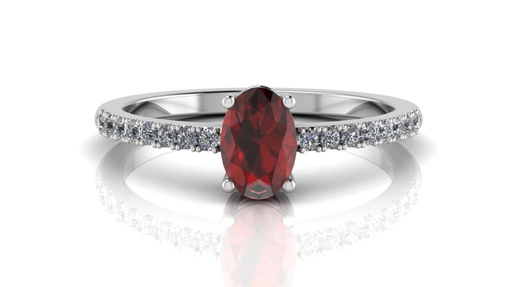 White gold ring featuring an oval cut garnet with diamonds