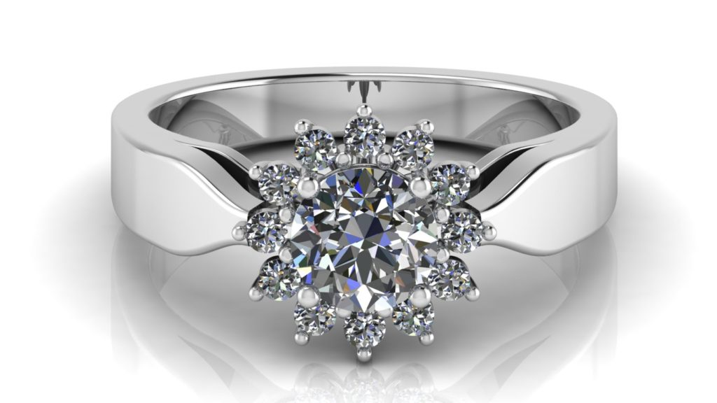 White gold cluster style engagement ring featuring a claw set round diamond and smaller surrounding diamonds