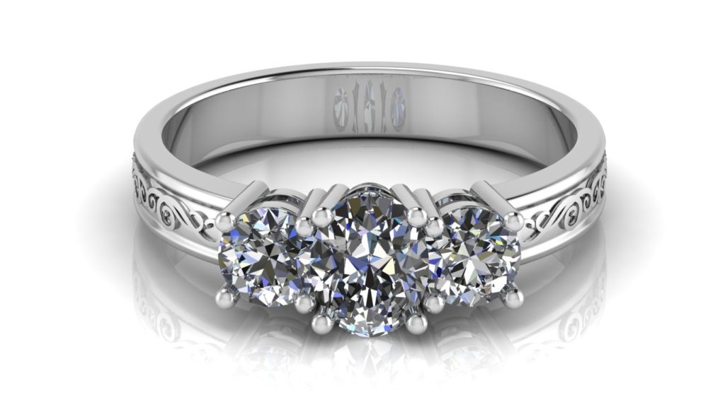 White gold three stone engagement ring featuring a claw set oval cut diamond with two side round diamonds and swirl motif
