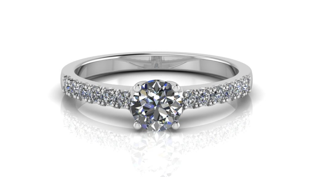 White gold engagement ring featuring a claw set round diamond with smaller diamonds down the band