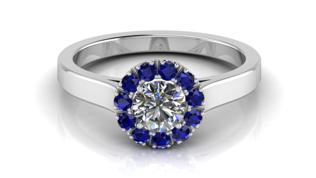 White gold halo engagement ring featuring a round diamond and smaller ceylon sapphires