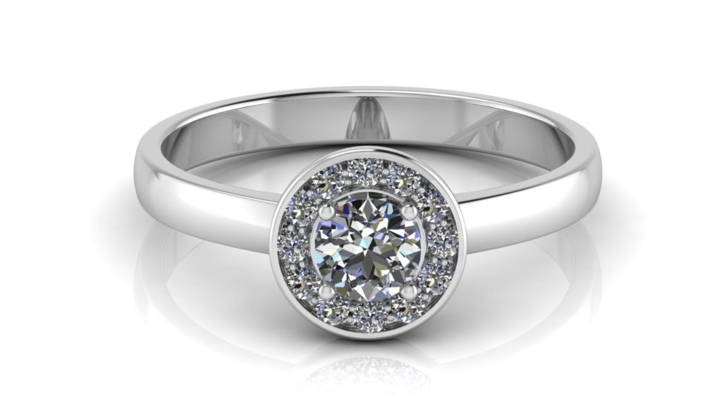 White gold engagement ring featuring a bezel set round diamond with a pave set diamond halo