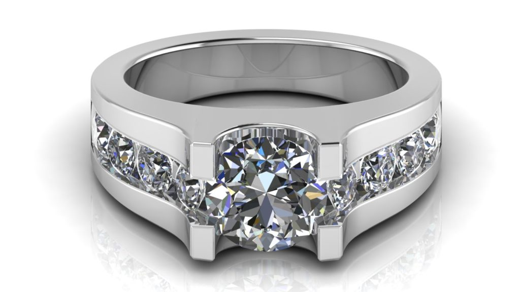 White gold engagement ring featuring a round diamond with smaller channel set diamonds down the band