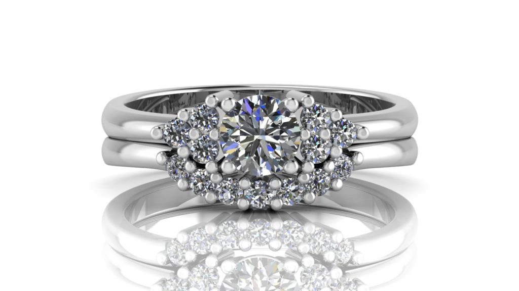 White gold engagement and matching wedding band featuring a round diamond with smaller diamonds set on the sides