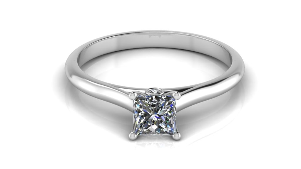 White gold solitaire engagement ring featuring a princess cut diamond with a bezel set accent diamond