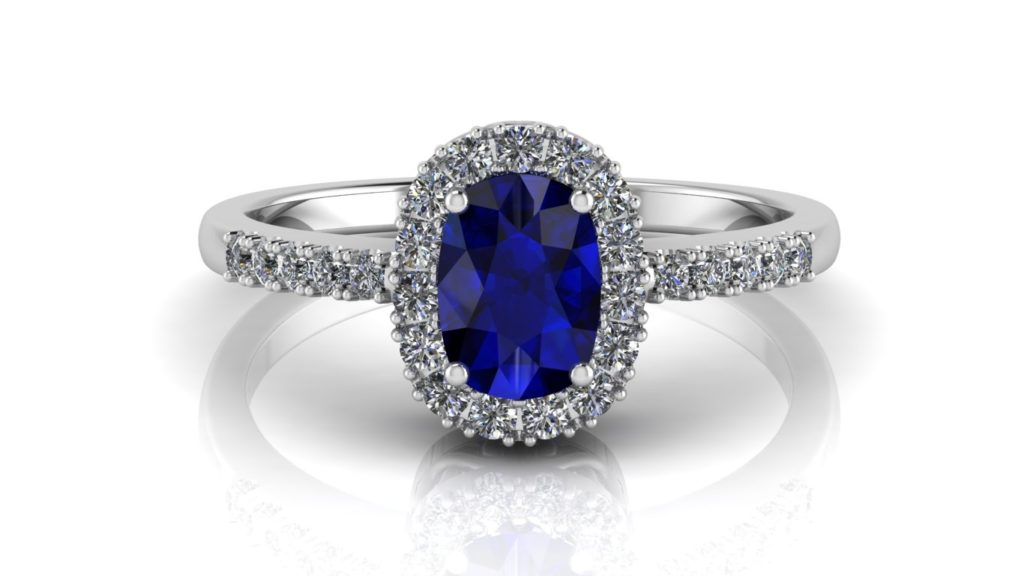 White gold halo engagement ring featuring an oval cut ceylon sapphire and smaller diamonds down the band